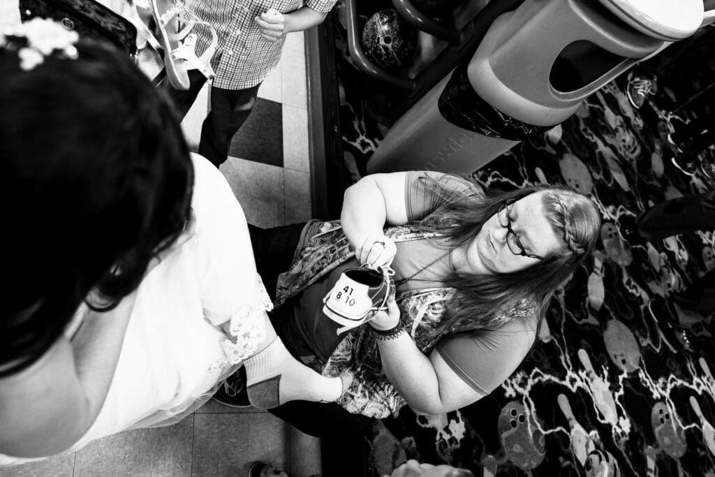 Putting on bowling shoes by La Crosse, WI Photographer Jeff Wiswell