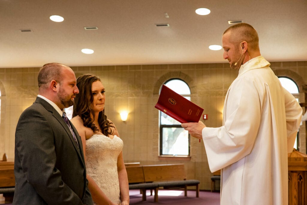 Couple with priest by La Crosse, WI Photographer Jeff Wiswell